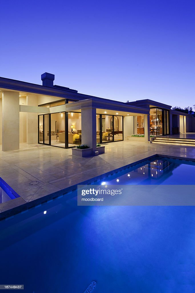 Rear view of luxury villa at night time with swimming pool : Stock Photo