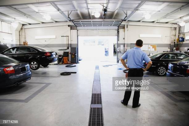 Rear view of male auto mechanic standing in auto repair shop