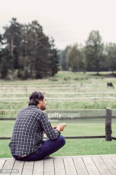 Rear view of male farmer sitting on porch at organic farm