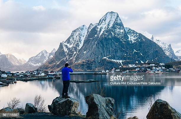 Rear view of male tourist photographing snow capped mountain and village waterfront, Reine, Lofoten, Norway