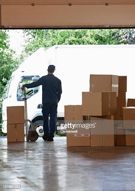 Rear view of male worker standing near cardboard cardboard boxes in warehouse