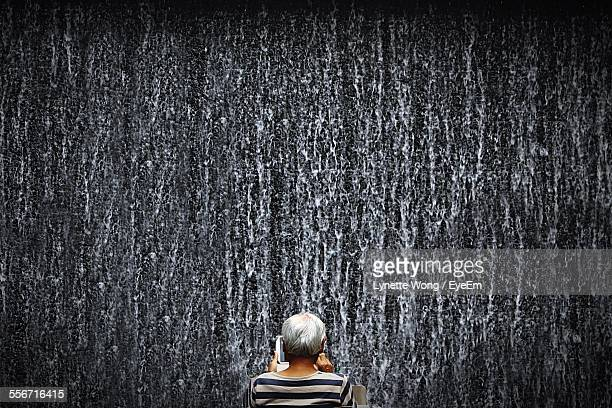 Rear View Of Man Against Artificial Waterfall