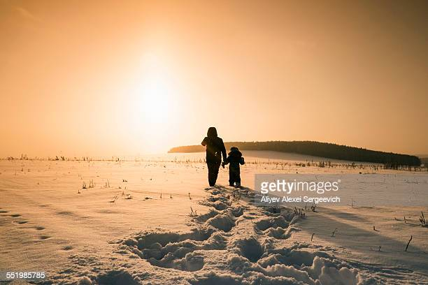 Rear view of man and son walking in snow covered landscape at sunset, Sarsy village, Sverdlovsk Oblast, Russia