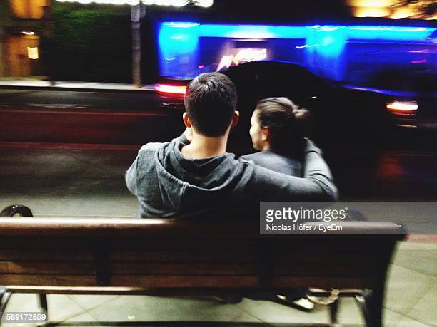 Rear View Of Man And Woman Sitting On Bench