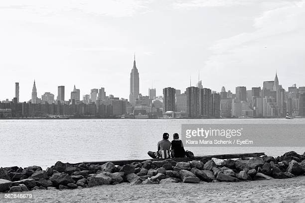 Rear View Of Man And Woman Sitting On Retaining Wall In Front Of Hudson River