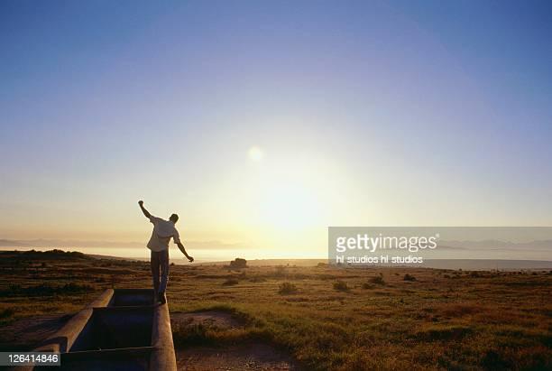 Rear view of man balancing on beach