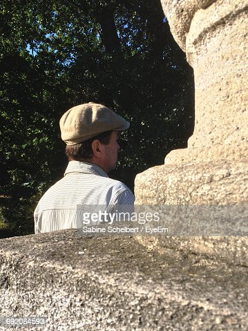 Rear View Of Man By Built Structure Against Tree