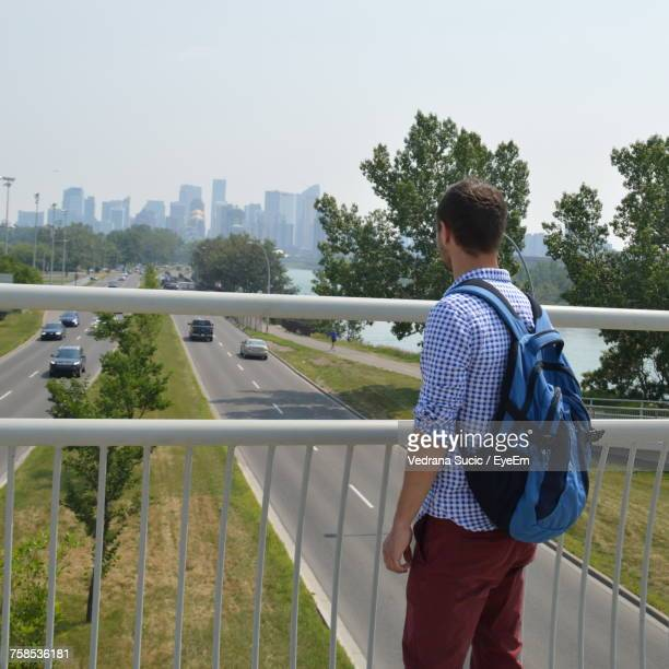 Rear View Of Man Carrying Backpack While Standing On Bridge Over Road