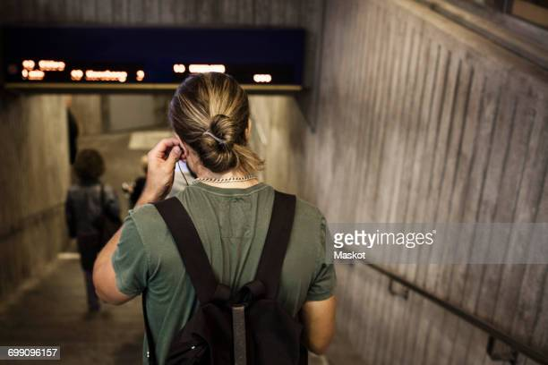 Rear view of man carrying backpack while walking down steps at subway station