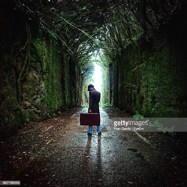 Rear View Of Man Carrying Luggage In Overgrown Tree Tunnel