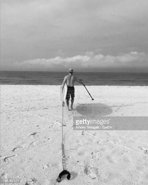 Rear View Of Man Carrying Paddleboard Towards Sea Against Cloudy Sky