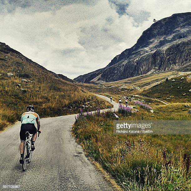 Rear View Of Man Cycling On Mountain Road Against Sky
