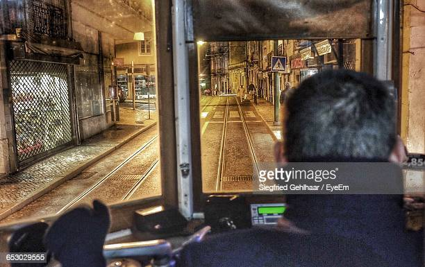 Rear View Of Man Driving Tram On Street In City At Night