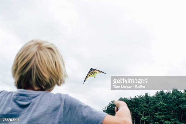 Rear View Of Man Flying Against Sky