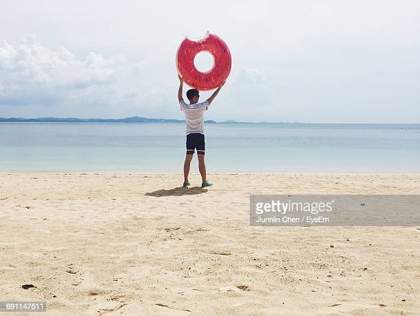 Rear View Of Man Holding Donut Shape Inflatable Ring At Beach Against Sky