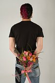 Rear view of man holding flowers behind back