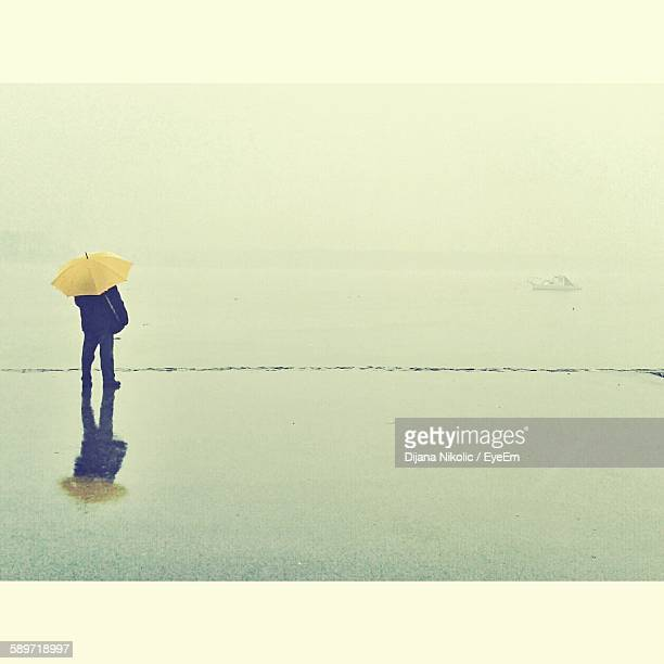 Rear View Of Man Holding Yellow Umbrella While Standing On Beach During Rainy Season