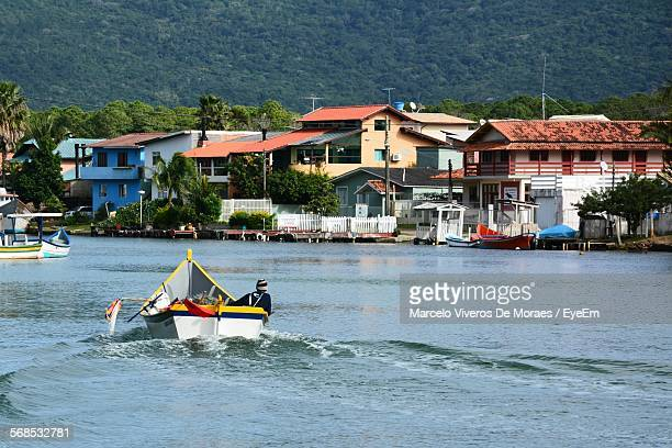 Rear View Of Man In Boat Sailing On Sea By Houses At Shore