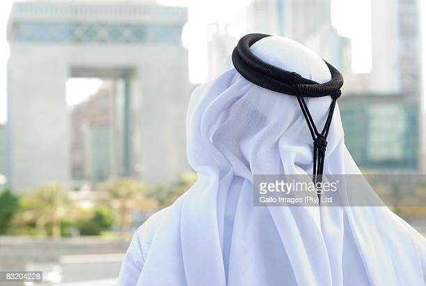 Rear view of man in Middle Eastern traditional attire looking at Dubai cityscape, UAE
