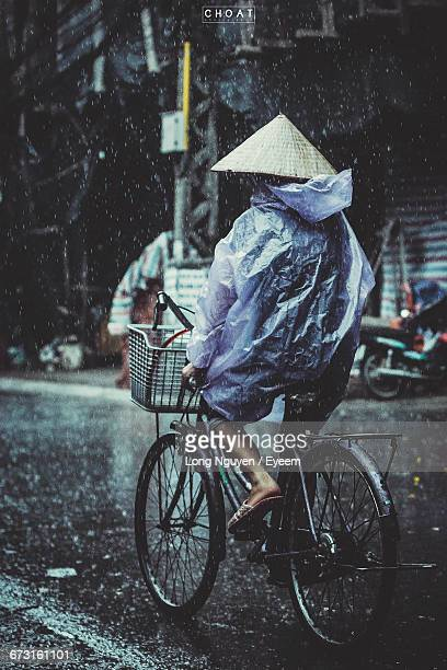 Rear View Of Man In Raincoat Riding Bicycle During Rainy Season