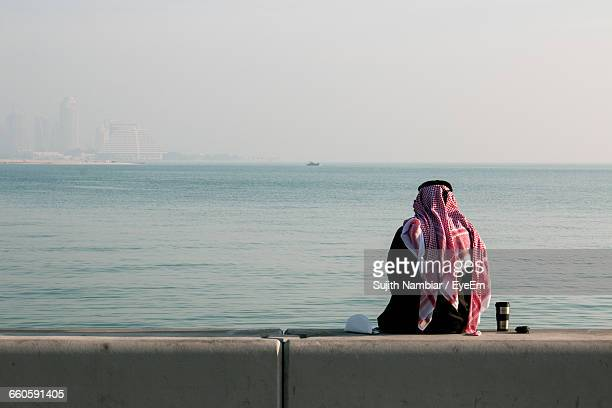 Rear View Of Man In Traditional Clothing While Sitting By Sea