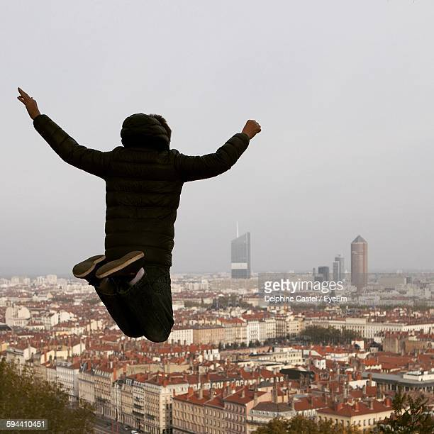 Rear View Of Man Jumping Mid-Air Against Cityscape