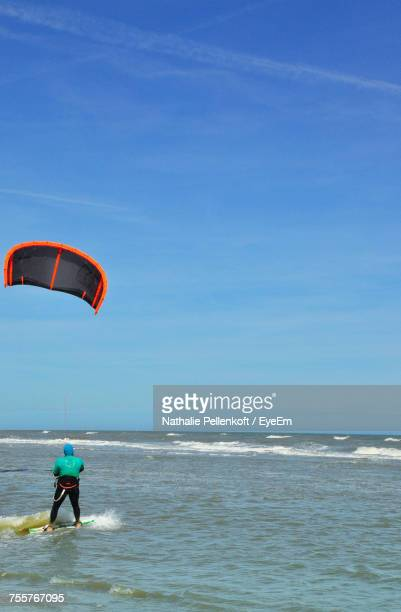 Rear View Of Man Kiteboarding On Sea Against Blue Sky During Sunny Day
