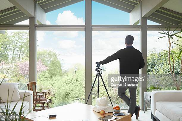 Rear view of man leaning on telescope looking out of window admiring garden scenic