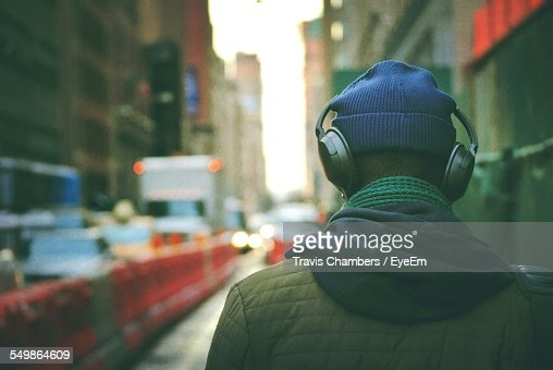 Rear View Of Man Listening To Music In Street