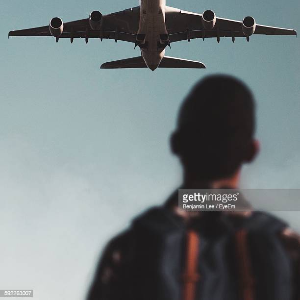 Rear View Of Man Looking At Airplane Flying At Sky