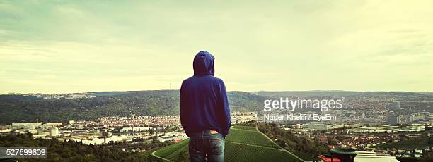 Rear View Of Man Looking At Cityscape Against Sky