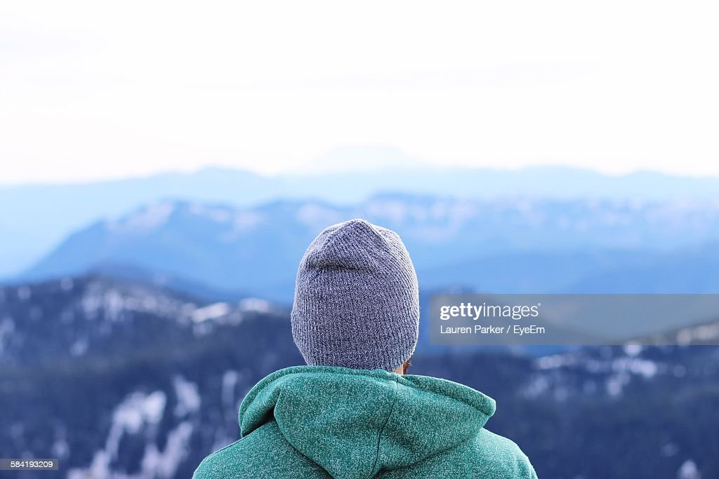 Rear View Of Man Looking At Mountains Against Clear Sky : Stock Photo