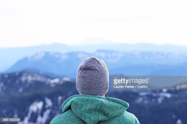 Rear View Of Man Looking At Mountains Against Clear Sky