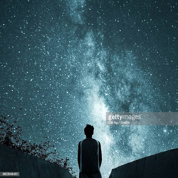 Rear View Of Man Looking At Star Field In Sky At Night
