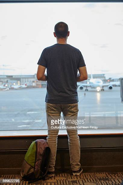 Rear view of man looking out of window at airport