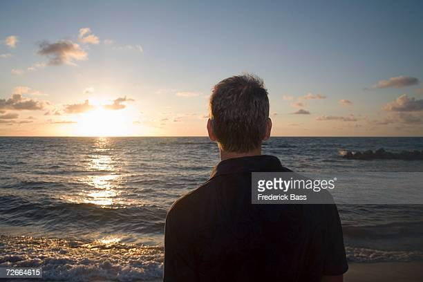 Rear view of man looking out to sea
