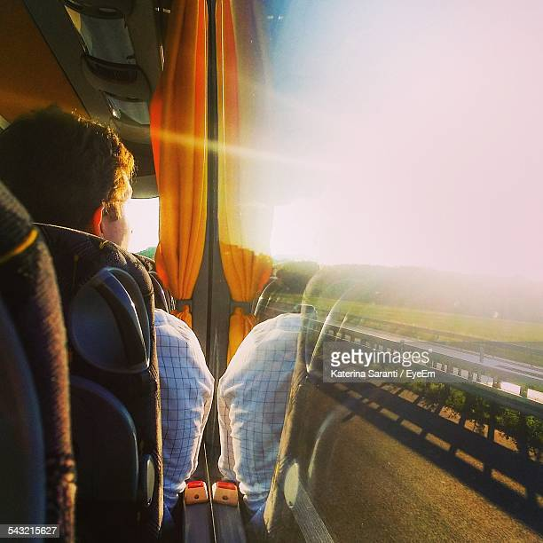 Rear View Of Man Looking Through Bus Window