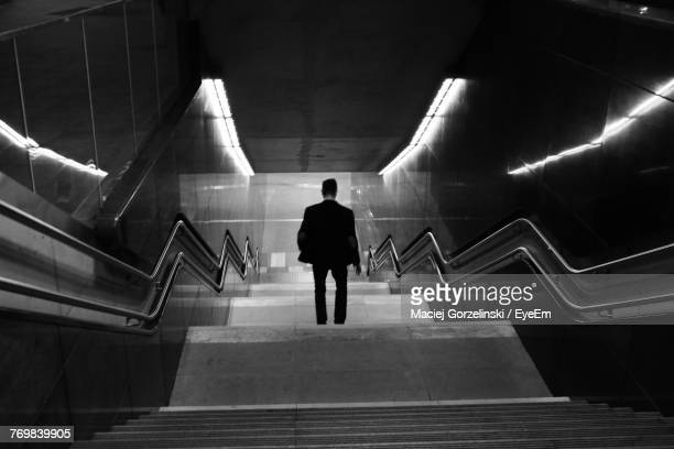 Rear View Of Man Moving Down Steps