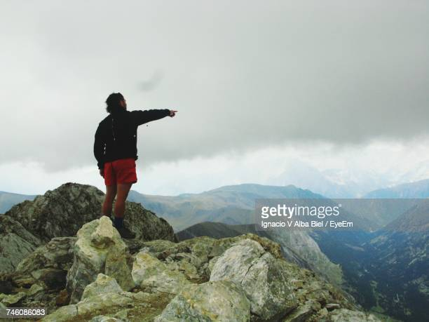 Rear View Of Man On Cliff Pointing Fingers Towards Mountains