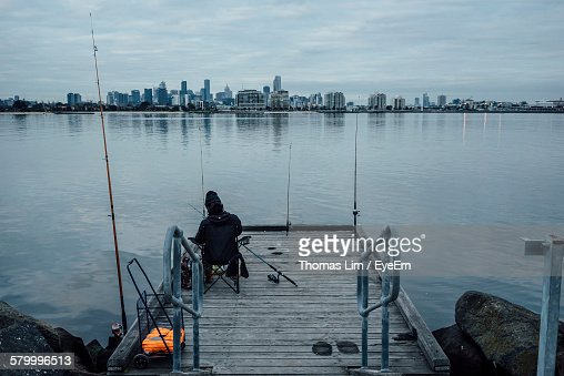 Rear View Of Man On Jetty In Sea Against Skyline