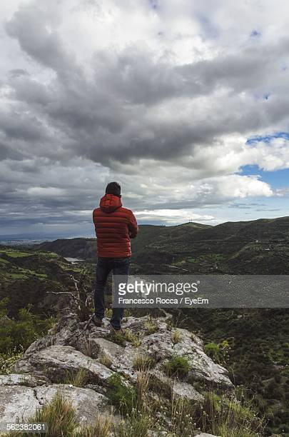 Rear View Of Man On Mountain Against Cloudy Sky