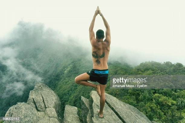 Rear View Of Man Performing Tree Pose On Mountains