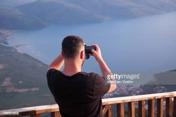Rear View Of Man Photographing Sea With Mobile Phone While Standing By Wooden Railing