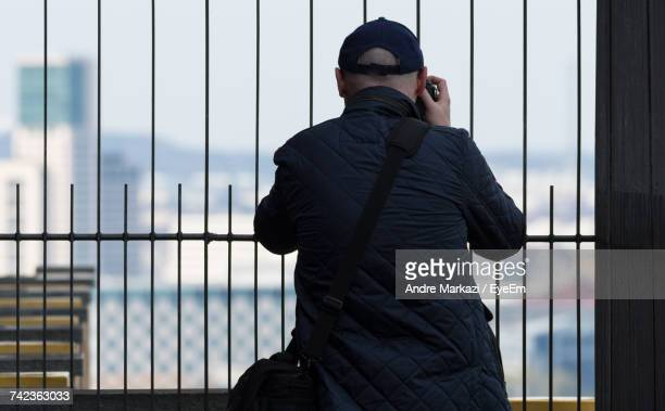 Rear View Of Man Photographing With Camera While Standing By Metal Fence In City