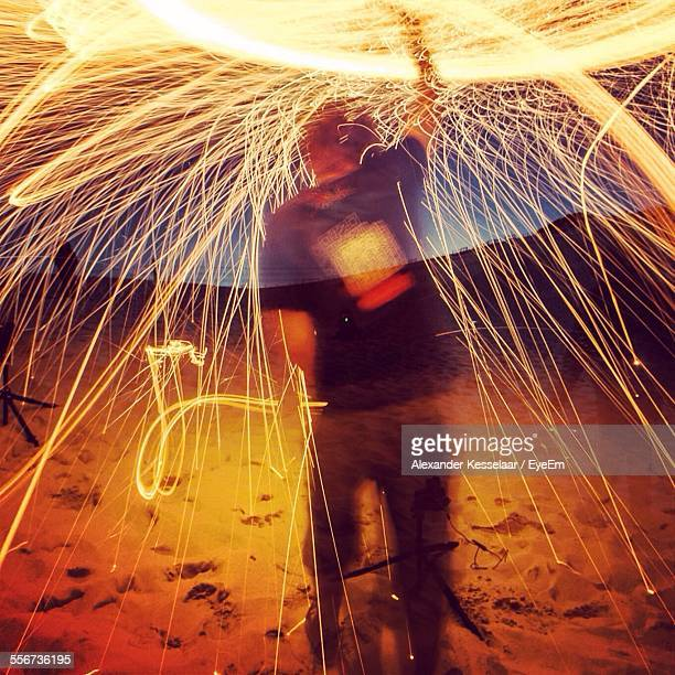 Rear View Of Man Playing With Sparkler