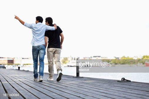 Rear view of man pointing at something to friend while walking on pier