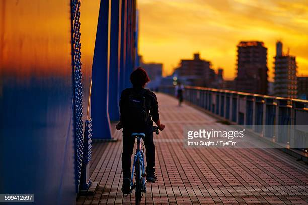 Rear View Of Man Riding Bicycle On Bridge In City During Sunset