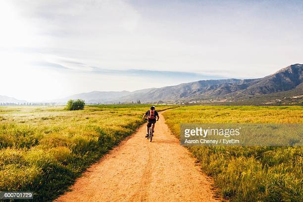 Rear View Of Man Riding Bicycle On Street Amidst Grassy Field Against Sky