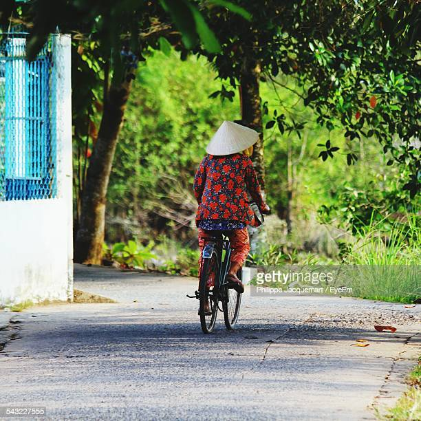 Rear View Of Man Riding Bicycle On Street In City