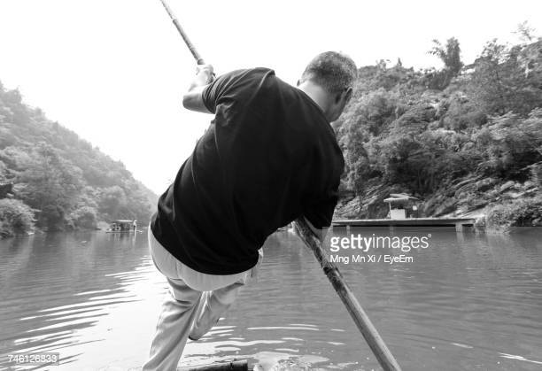 Rear View Of Man Rowing Boat At Lake
